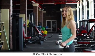 woman doing biceps workout with dumbbell - Young fitness...