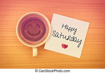 Happy Saturday on paper note with coffee cup,top view.