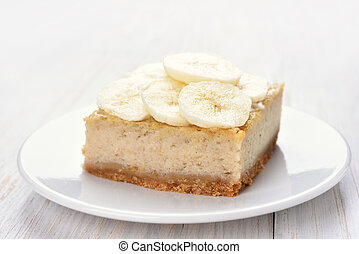 Banana cheese cake on white wooden table, close up view