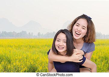 girls smiling in flower field