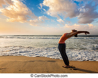 Woman doing yoga Sun salutation Surya Namaskar - Young...