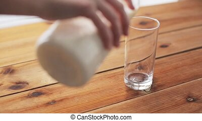 hand pouring milk into glass on wooden table - healthy...