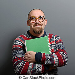 Portrait of a nerd holding book with retro glasses against gray background