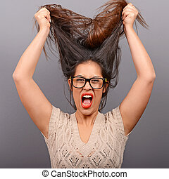 Portrait of a histerical woman pulling hair out against gray...