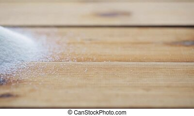 white sugar pouring into heap on wooden table