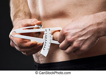 Man is measuring his body fat with calipers. - Young man is...