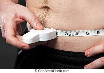Man measuring his waist - Man measuring his waist with a...
