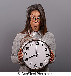 Portrait of business woman holding clock against gray...