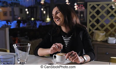attractive brunette sits at a bar and drinking coffee. Great...
