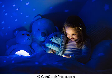Little girl reading a book in bed Dark bedroom with night...