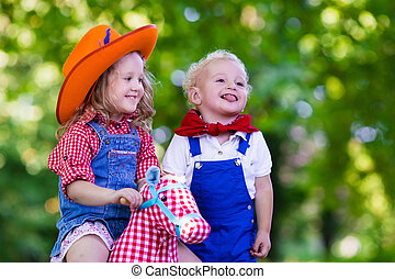 Cowboy kids playing with toy horse - Little boy and girl...