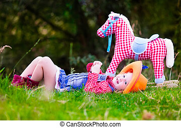 Little girl playing with toy horse in cowboy costume -...