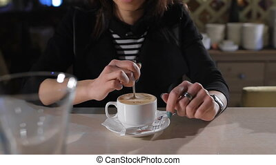 attractive brunette sits at a bar and drinking coffee. Great mood, she laughs