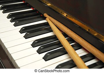 Diagonal shot of drum sticks on piano keyboard - Drum sticks...
