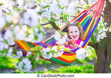 Little girl relaxing in a hammock - Child relaxing in...