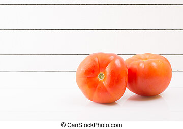 Two ripe tomatoes on a light background propped up - Two...