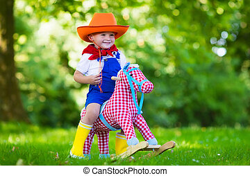 Child playing with a toy horse - Little boy dressed up as...