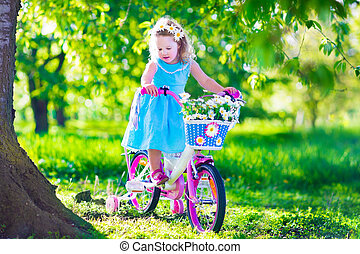 Little girl riding a bike - Happy child riding a bike. Cute...