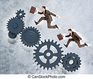 Two businessmen running on wheel gears on grey wall...