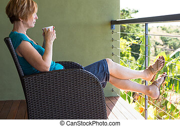 Woman sitting with feet up - Woman relaxing drinking tea /...