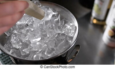 The bartender pulls out the ice cubes for a cocktail, using...