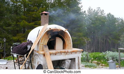 """brick, clay oven fire outdoor in forest garden background"""