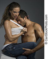 erotic scene of a sexy couple in jeans having sex - a man...