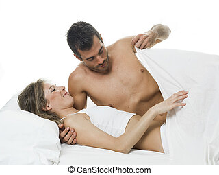 funny couple foreplaying in a white bed and sheets - a man...