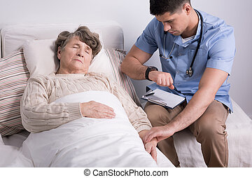 Checking the pulse - Shot of an old woman laying on bed and...