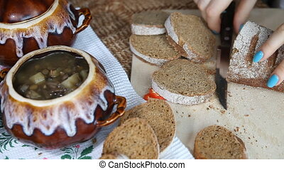 Woman cut into bread Nearby there is a lean food in a pot -...