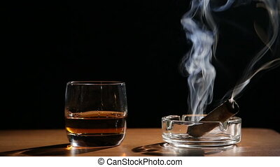 Whiskey drinks with smoking cigars - Glass of whiskey with...