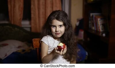 Teen girl eating an apple sitting in the room in evening -...
