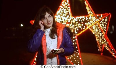 girl in a jacket listening to music on smartphone winter...