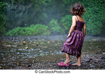 Three year old girl standing at the base of a large waterfall