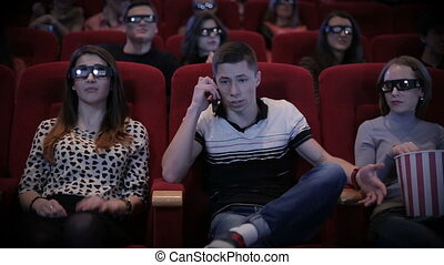 Man talking by phone at cinema and disturbs other people