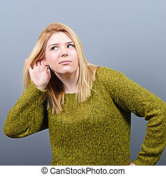 Portrait of woman trying to listen something against gray...