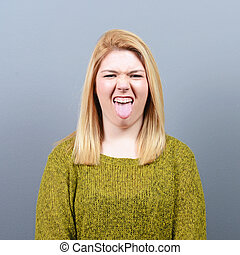 Portrait of woman sticking out her tongue against gray...