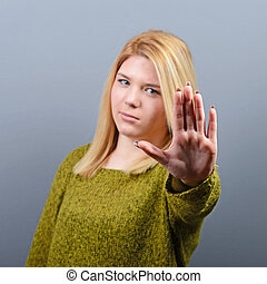 Portrait of woman showing stop with hand against gray...