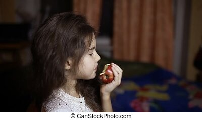 girl teen eating an apple sitting in room in evening