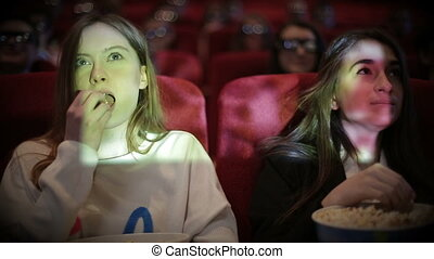 Teenage girls watching movie in cinema - Two Young woman...