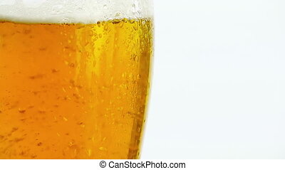 detail of pouring fresh beer with foam into glass on white background