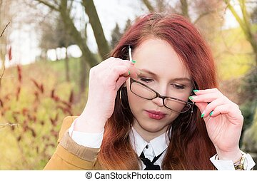 Woman puts glasses on - A young woman is wearing glasses...