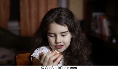 girl teen eating an apple sitting in the room in evening -...