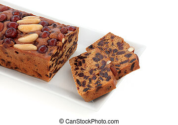 Genoa Cake - Genoa fruit cake with slices on a plate over...