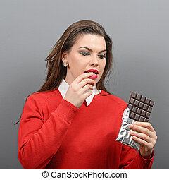 Beautiful woman in temptation of eaiting a chocolate against...