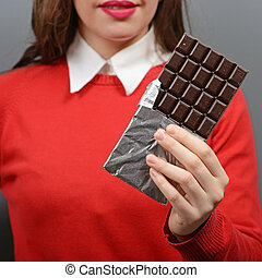 Close up of woman holding chocolate against gray background
