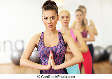 Group of women doing yoga in gym