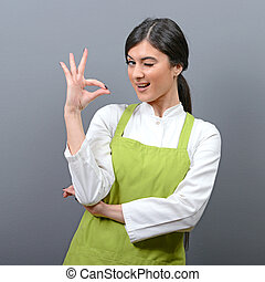Portrait of beautiful woman chef showing ok sign against...