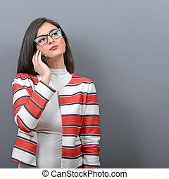 Portrait of businesswoman using cellphone against gray...