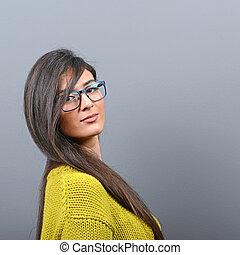 Portrait of beautiful woman with glasses posing against gray background